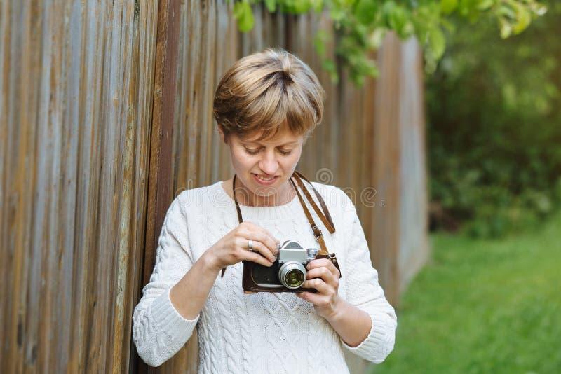 Ragazza con la retro macchina fotografica della foto vicino al recinto all'aperto immagine stock