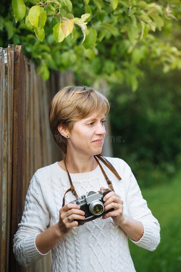 Ragazza con la retro macchina fotografica della foto vicino al recinto all'aperto immagine stock libera da diritti
