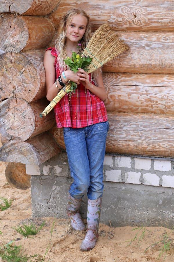 Ragazza con la scopa ed i fiori fotografie stock