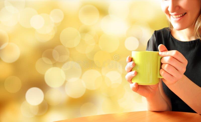 Ragazza con la tazza di tè su priorità bassa luminosa fotografie stock libere da diritti