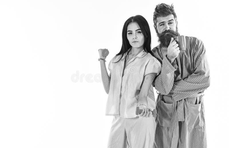 Ragazza con la testa di legno, uomo con la tazza di caffè, isolata su fondo bianco Le coppie nell'amore in pigiama, accappatoio s fotografia stock