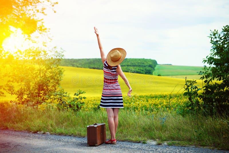 Ragazza con la vecchia valigia che sta sul bordo della strada in sole fotografia stock libera da diritti