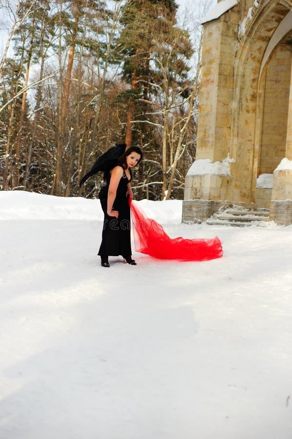 Ragazza con le ali nere di angelo in un vestito nero nell'inverno ed in tessuto scorrente rosso immagine stock
