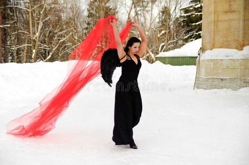 Ragazza con le ali nere di angelo in un vestito nero nell'inverno ed in tessuto scorrente rosso fotografia stock libera da diritti