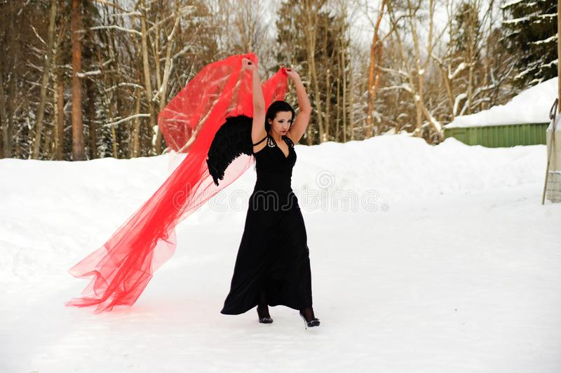 Ragazza con le ali nere di angelo in un vestito nero nell'inverno ed in tessuto scorrente rosso fotografia stock