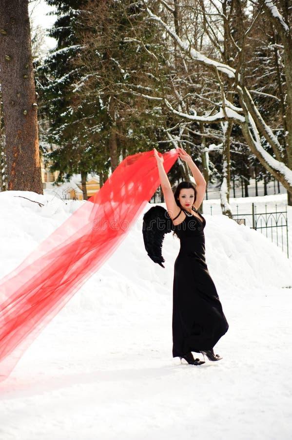 Ragazza con le ali nere di angelo in un vestito nero nell'inverno ed in tessuto scorrente rosso immagini stock