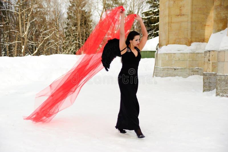 Ragazza con le ali nere di angelo in un vestito nero nell'inverno ed in tessuto scorrente rosso immagine stock libera da diritti