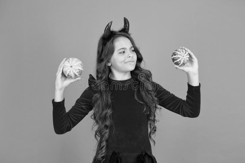 Ragazza con le corna gioca con le zucche Buone feste Bambini carini festeggiano Halloween Divertiti Festività autunnali fotografie stock libere da diritti