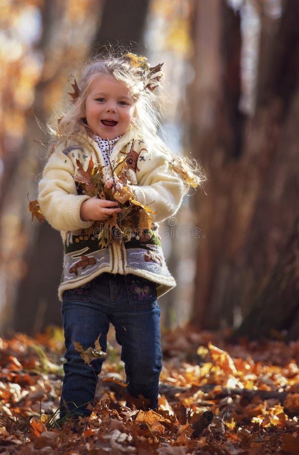 Ragazza con le foglie di autunno variopinte fotografia stock