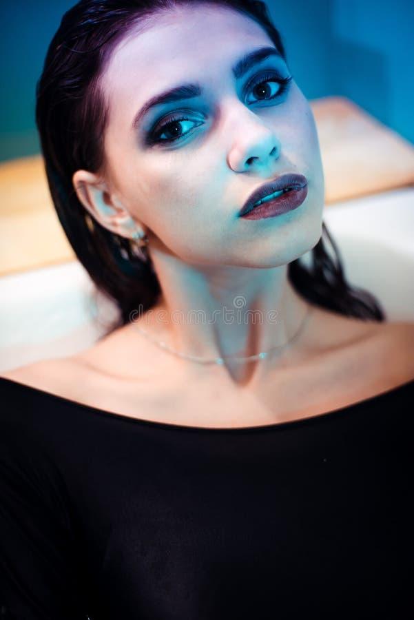 Ragazza con le spalle nude che si trovano nel bagno con acqua porpora colorata Concetto di modo immagini stock
