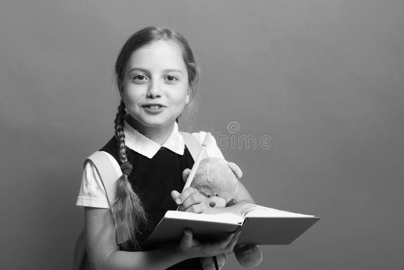 Ragazza con le trecce ed il fronte felice Bambino in uniforme scolastico fotografia stock