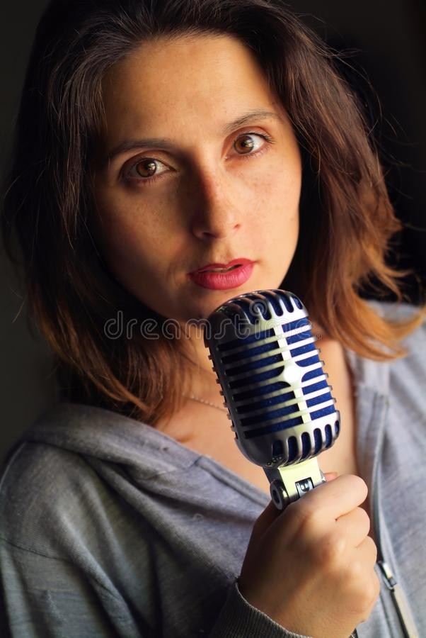 Ragazza con lo sguardo ipnotico con un microfono immagini stock libere da diritti