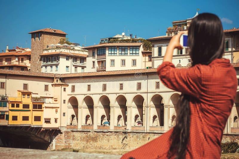 Ragazza con lo smartphone che fa immagine del Arno vicino al ponte famoso città antica di Firenze, Toscana in Italia fotografia stock libera da diritti