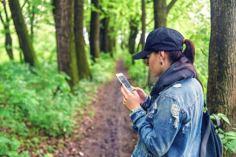 Ragazza con lo smartphone nella foresta immagine stock