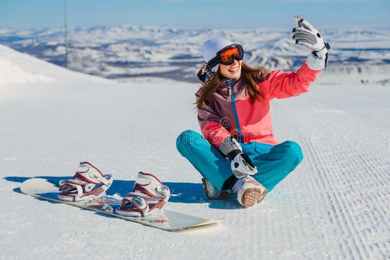 Ragazza con lo snowboard che si siede e che prende i selfies nelle montagne immagini stock libere da diritti