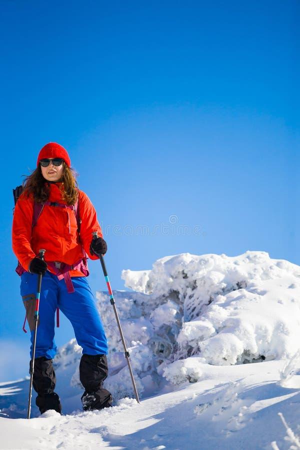 Ragazza con lo zaino che cammina sulla neve nelle montagne fotografia stock libera da diritti