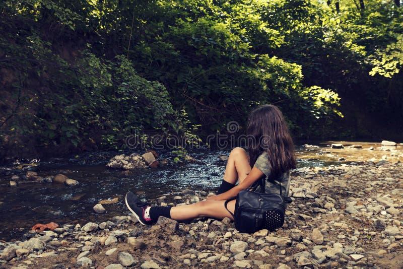 Ragazza con lo zaino nero che si siede da solo sopra su una sponda del fiume in un'ora legale del parco della città fotografia stock libera da diritti