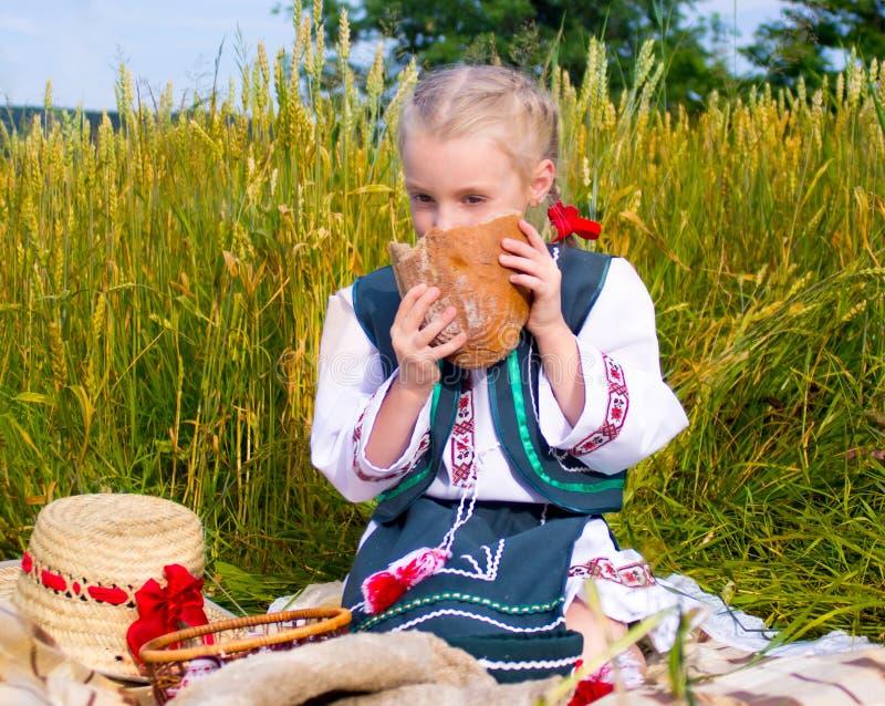 Ragazza con pane al campo fotografia stock libera da diritti