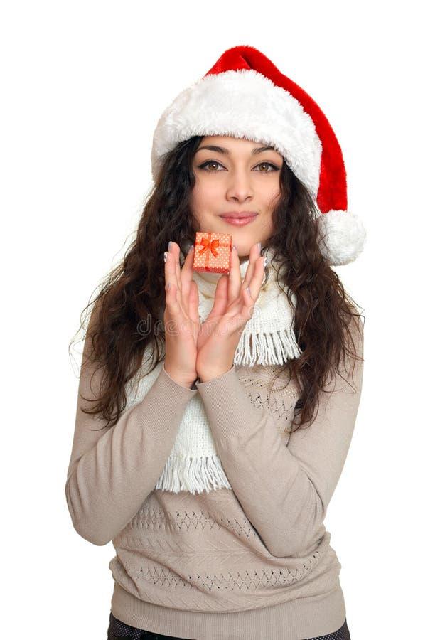 Ragazza con poco contenitore di regalo in ritratto del cappello di Santa, posante sul fondo, sul concetto di festa di natale, su  fotografia stock