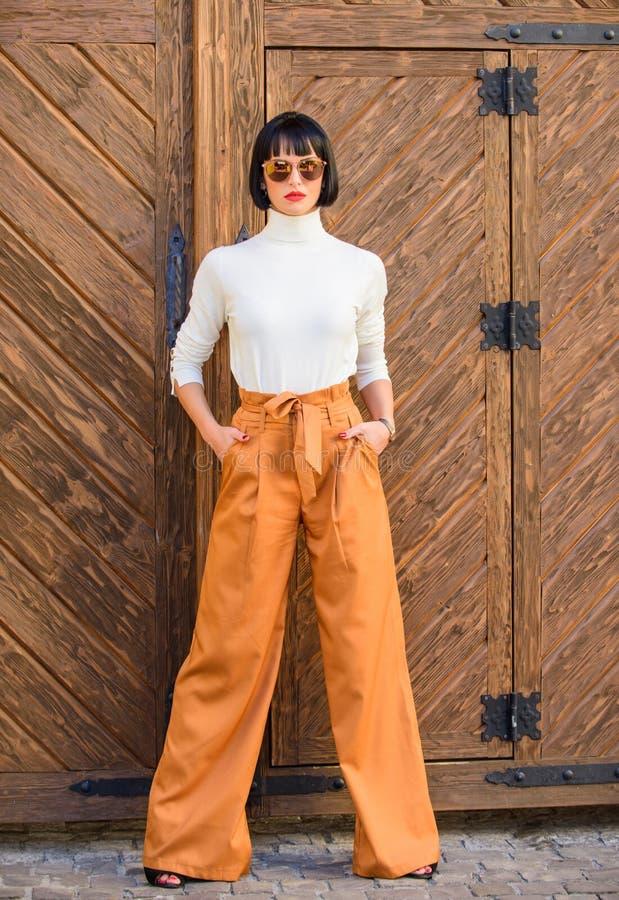 Ragazza con trucco che posa in vestiti alla moda Signora alta esile dell'attrezzatura alla moda concetto di stile e di modo Passe immagini stock