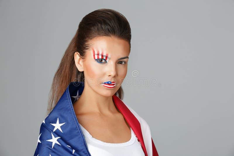 Ragazza con trucco di U.S.A. e bandiera su fondo grigio immagine stock libera da diritti