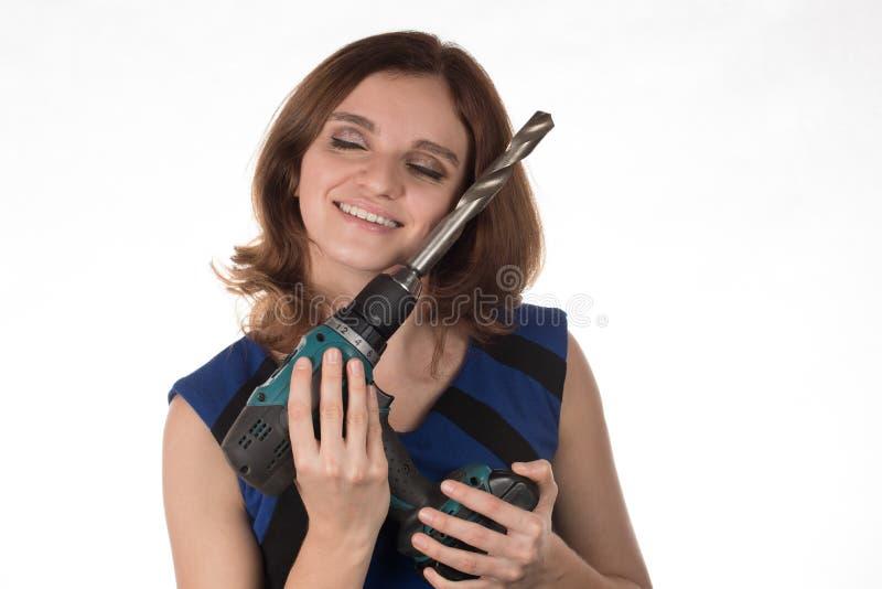 Ragazza con un cacciavite dell'attrezzo che ride su un backgro bianco fotografie stock