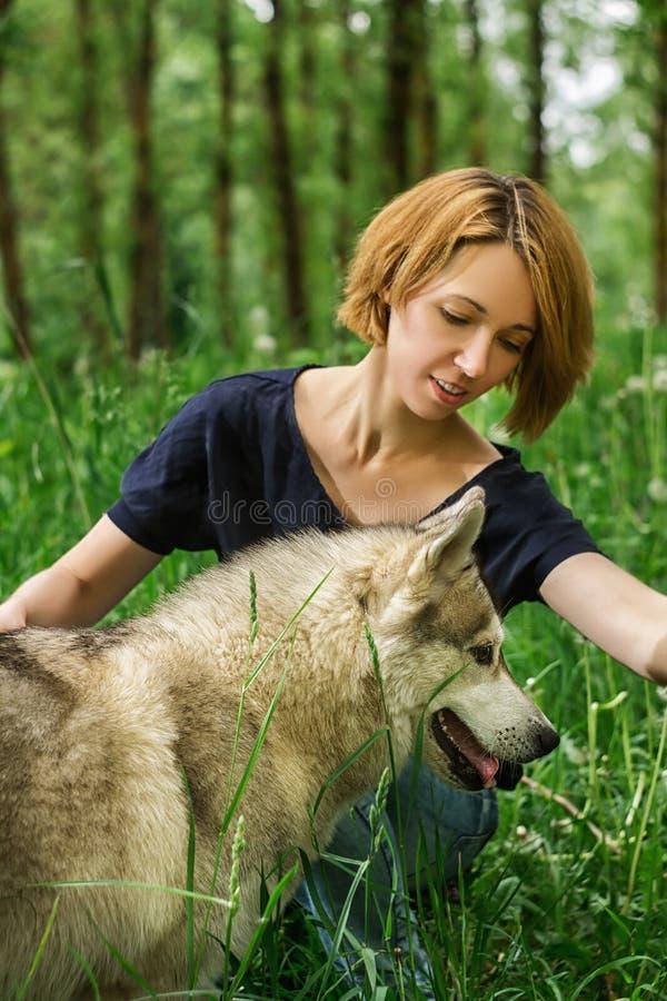 Ragazza con un cane nella natura fotografie stock libere da diritti