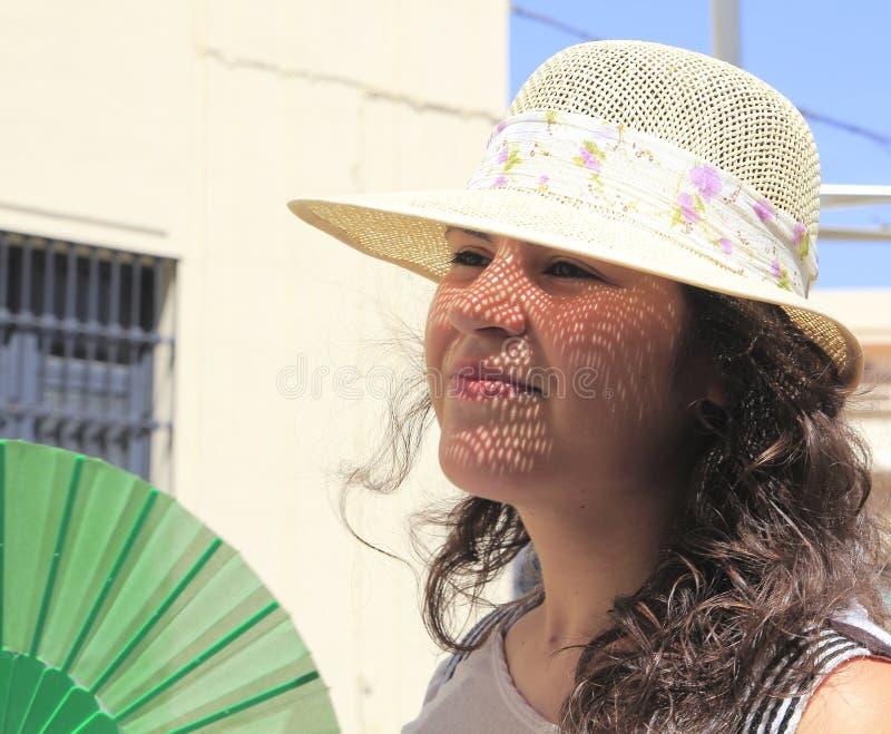 Ragazza con un cappello, con una griglia del sole sul suo fronte immagini stock libere da diritti