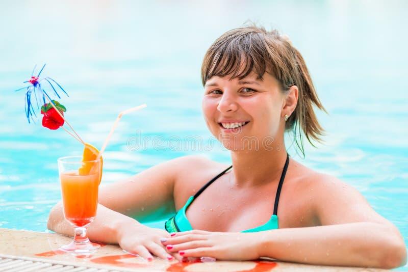 Ragazza con un cocktail alcolico in acqua immagine stock