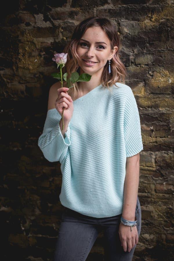 Ragazza con un fiore davanti al muro di mattoni fotografia stock libera da diritti