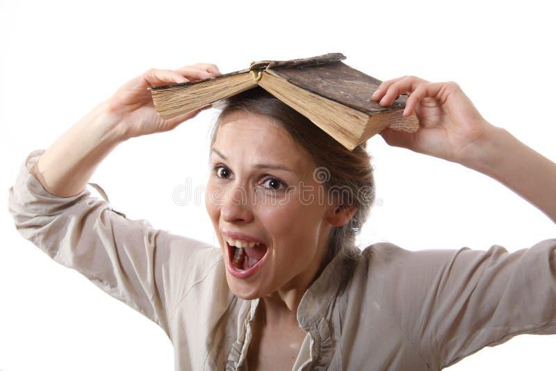 Ragazza con un libro sulla sua testa immagini stock libere da diritti