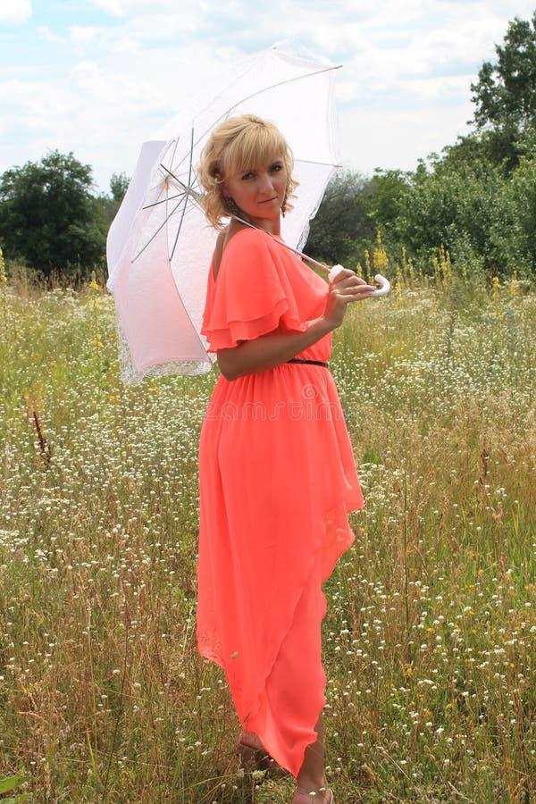 Ragazza con un ombrello bianco, un vestito lungo, un campo dei fiori, un vestito rosa bella ragazza bionda in un campo dei fiori fotografia stock
