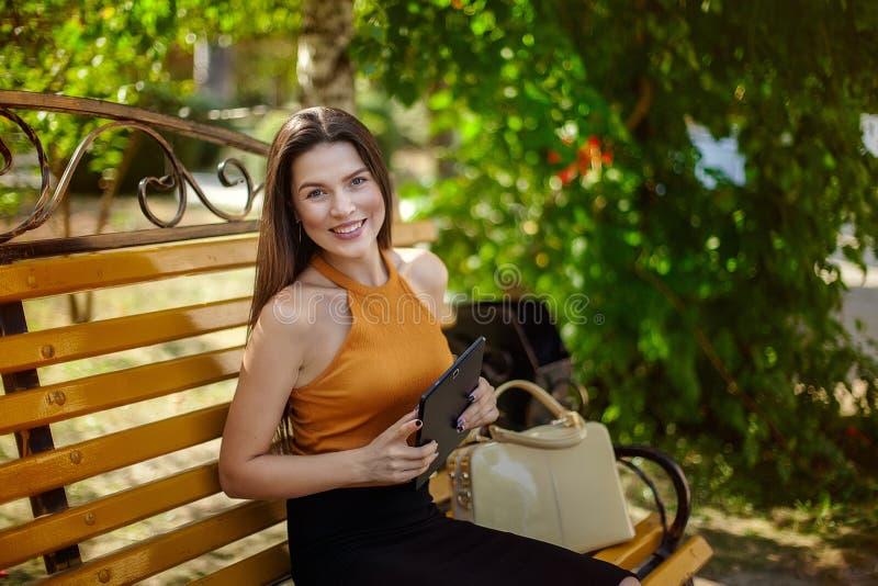 Ragazza con un ridurre in pani Donna allegra e felice di affari che si siede su un banco con una borsa e una compressa fotografia stock