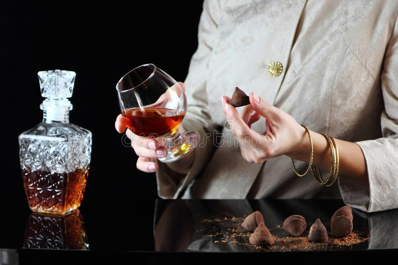 Ragazza con un vetro del cognac e della caramella immagine stock libera da diritti