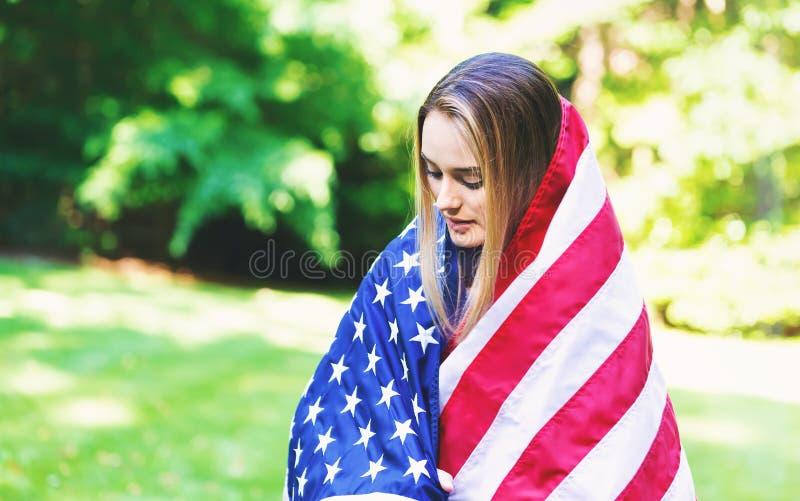 Ragazza con una bandiera americana sul quarto di luglio immagine stock libera da diritti