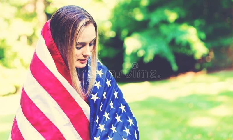 Ragazza con una bandiera americana sul quarto di luglio fotografia stock