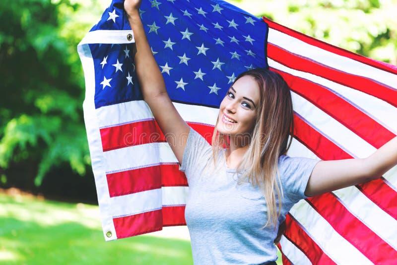 Ragazza con una bandiera americana sul quarto di luglio fotografie stock