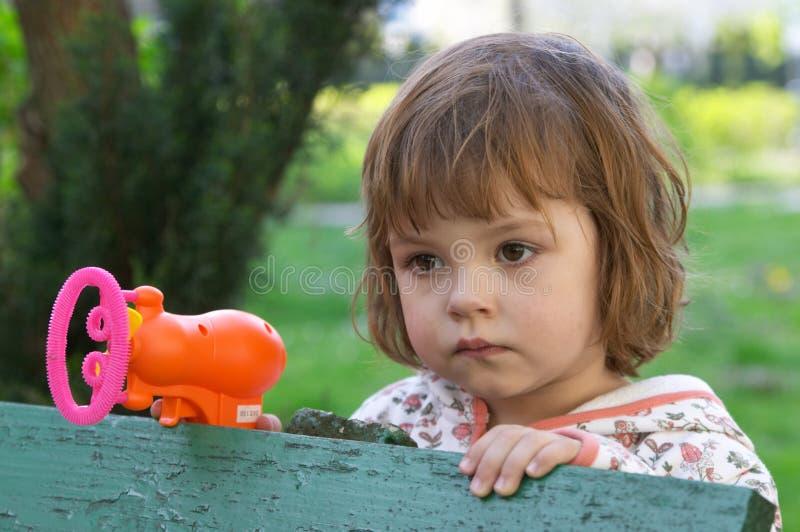 Ragazza con una bolla che fa pistola fotografia stock