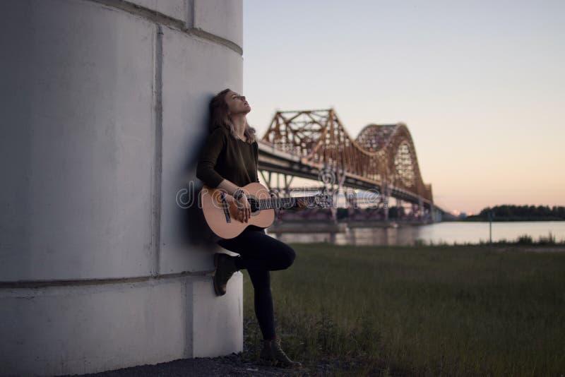 Ragazza con una chitarra che sta al piede del ponte sopra la r fotografia stock libera da diritti