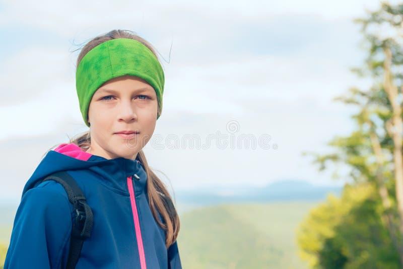 Ragazza con una fascia durante il viaggio della montagna che esamina direttamente la macchina fotografica immagine stock