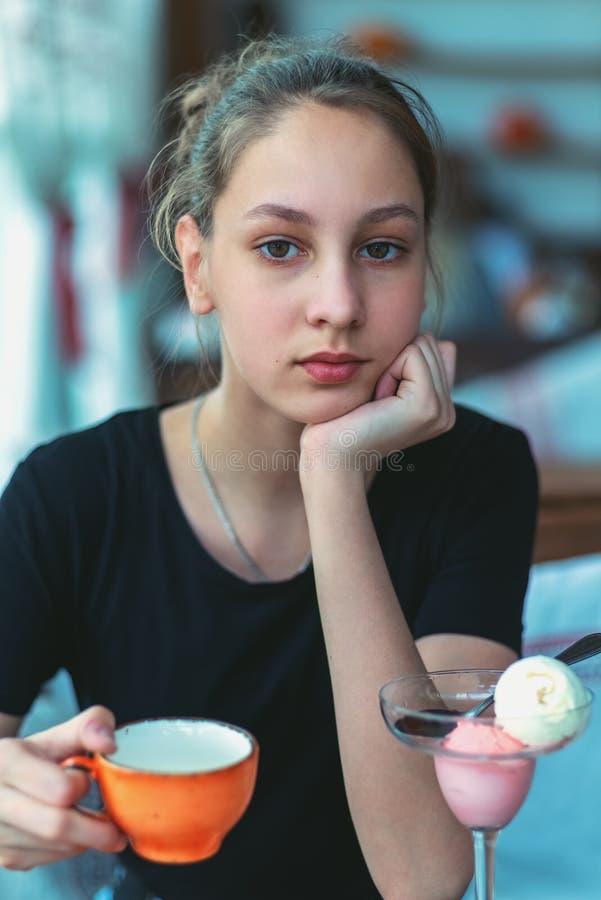 Ragazza con una tazza in suoi mano e gelato sulla tavola fotografia stock libera da diritti