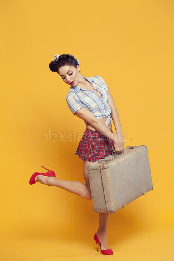 Ragazza con una valigia a disposizione turista in pin-up fotografie stock