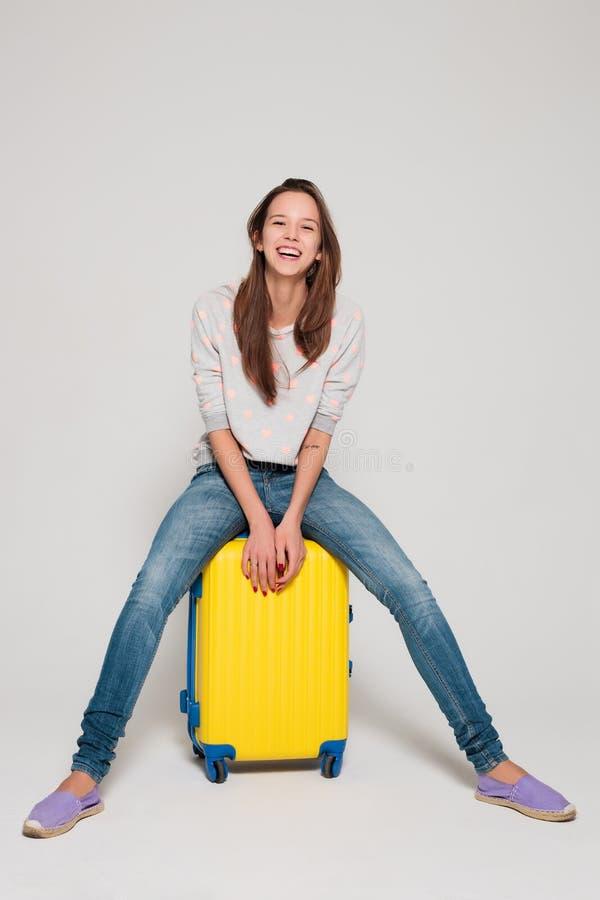 Ragazza con una valigia gialla immagine stock immagine - Immagine di una ragazza a colori ...