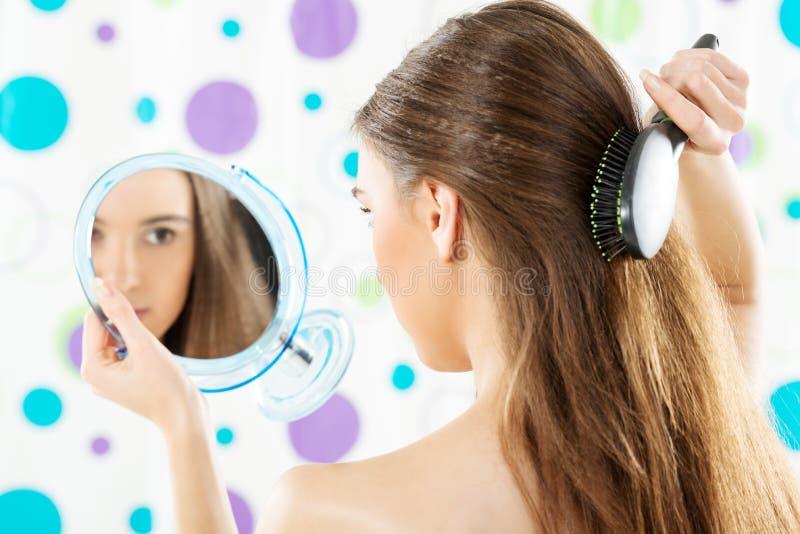 Ragazza con uno specchio che pettina i suoi capelli fotografia stock libera da diritti