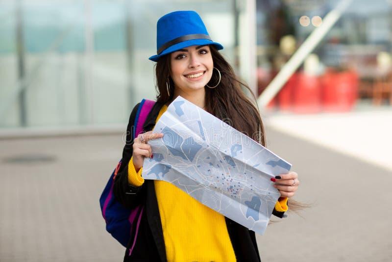 Ragazza con uno zaino dietro la sua spalla che tiene una mappa, nella via vicino all'aeroporto immagini stock