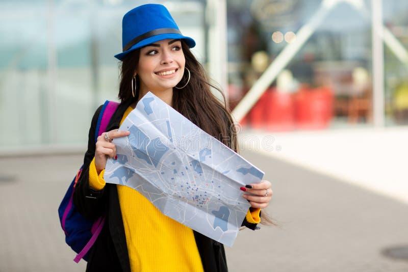 Ragazza con uno zaino dietro la sua spalla che tiene una mappa, nella via vicino all'aeroporto immagine stock