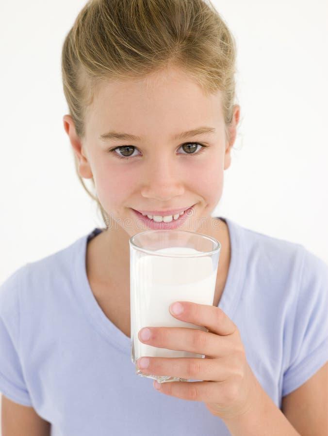 Ragazza con vetro di sorridere del latte immagine stock libera da diritti