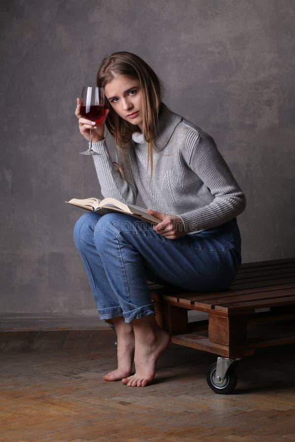 Ragazza con vino Fondo grigio immagine stock
