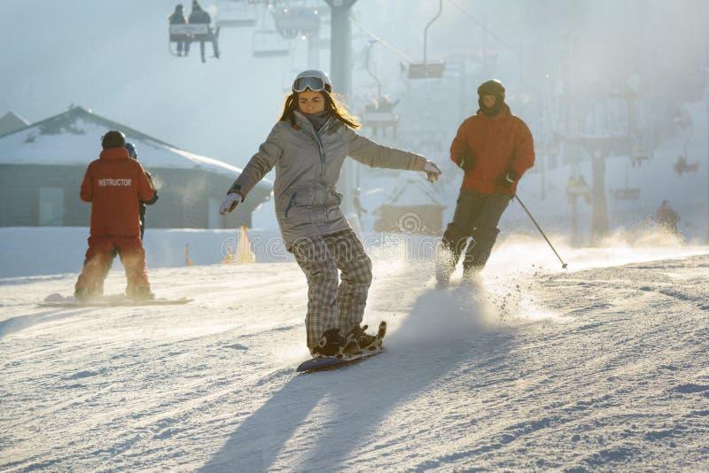 Ragazza concentrata sullo snowboard fotografie stock
