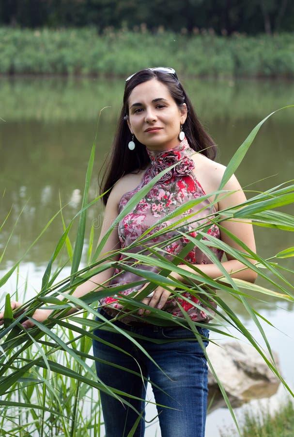 Ragazza contro il lago con una canna in una mano fotografia stock libera da diritti